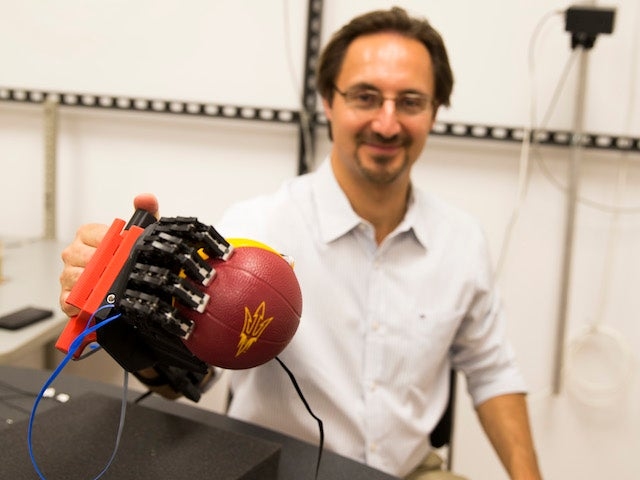 Neurophysiologist Marco Santello is collaborating on a project that employs new advances to simplify the control of grasping movements by a robotic hand. Photo by Jessica Hochreiter/ASU